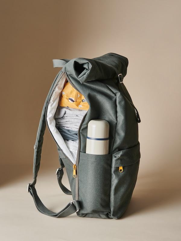 Un sac à dos DRÖMSÄCK vert dont la fermeture à glissière est ouverte d'un côté est rempli de vêtements et de sacs RENSARE. Il contient aussi un contenant isotherme HÄLSA.