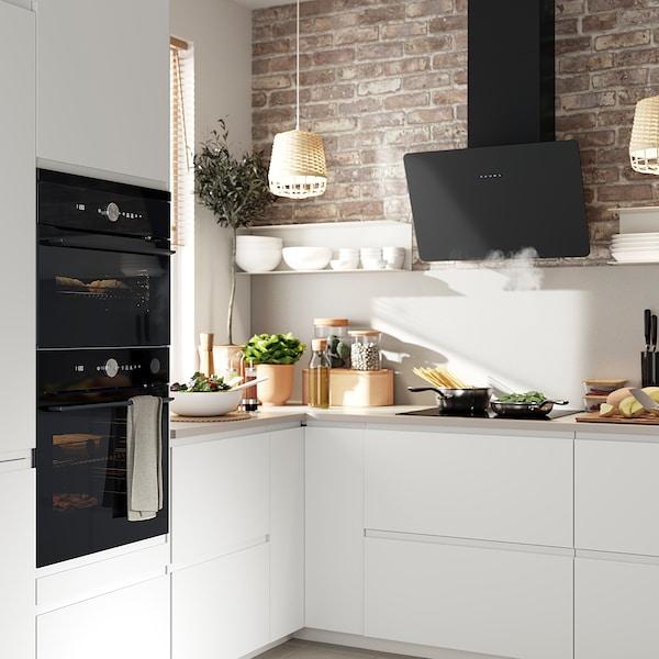 Valoisa keittiö, jossa on valkoiset VOXTORP- kaapin ovet. Keittiössä on FINSMAKARE-kiertoilma uuni ja -liesituuletin.
