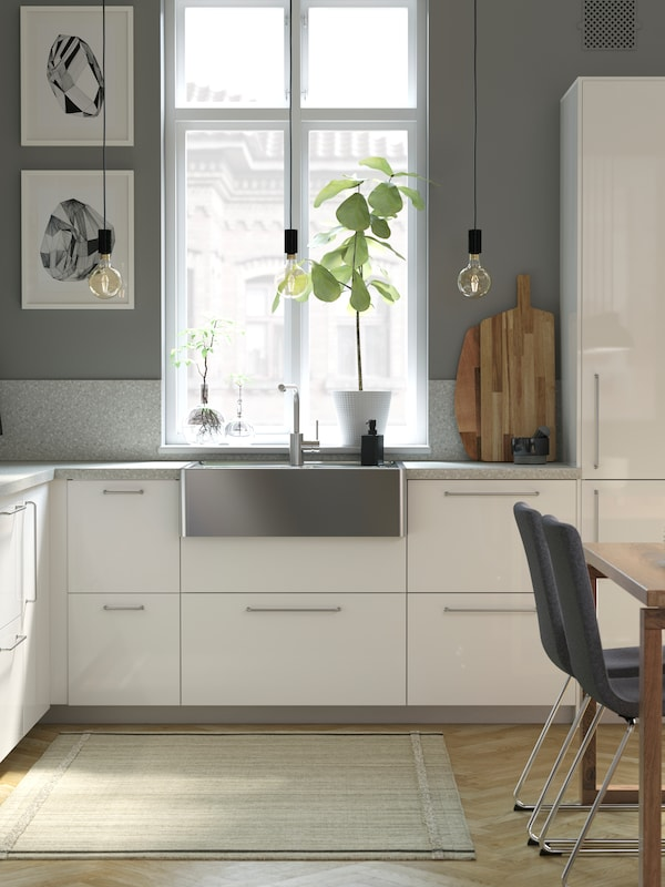 A white gloss kitchen with a metal sink