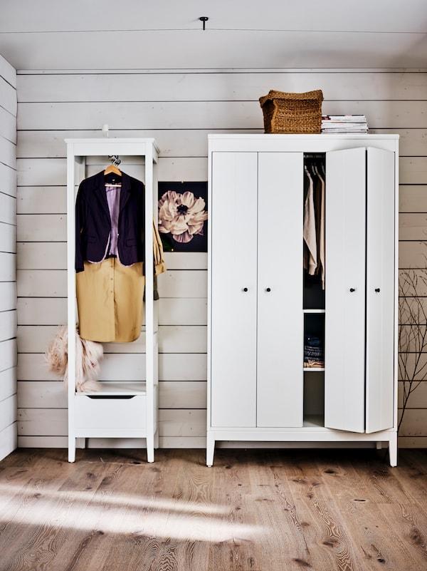 Ein weisser IDANÄS Kleiderschrank mit einem Korb obenauf, daneben ein IDANÄS offener Kleiderschrank. Beide sind mit Kleidung gefüllt.