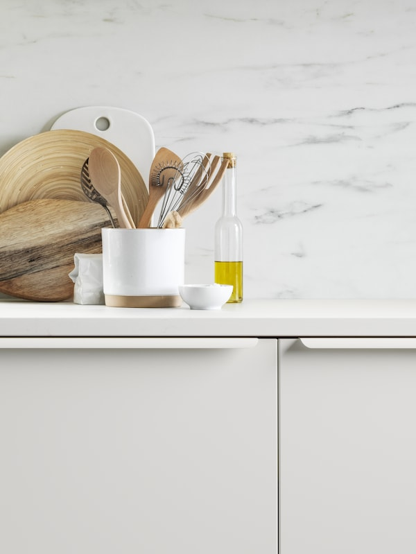 A white KASKER countertop covered with kitchen accessories