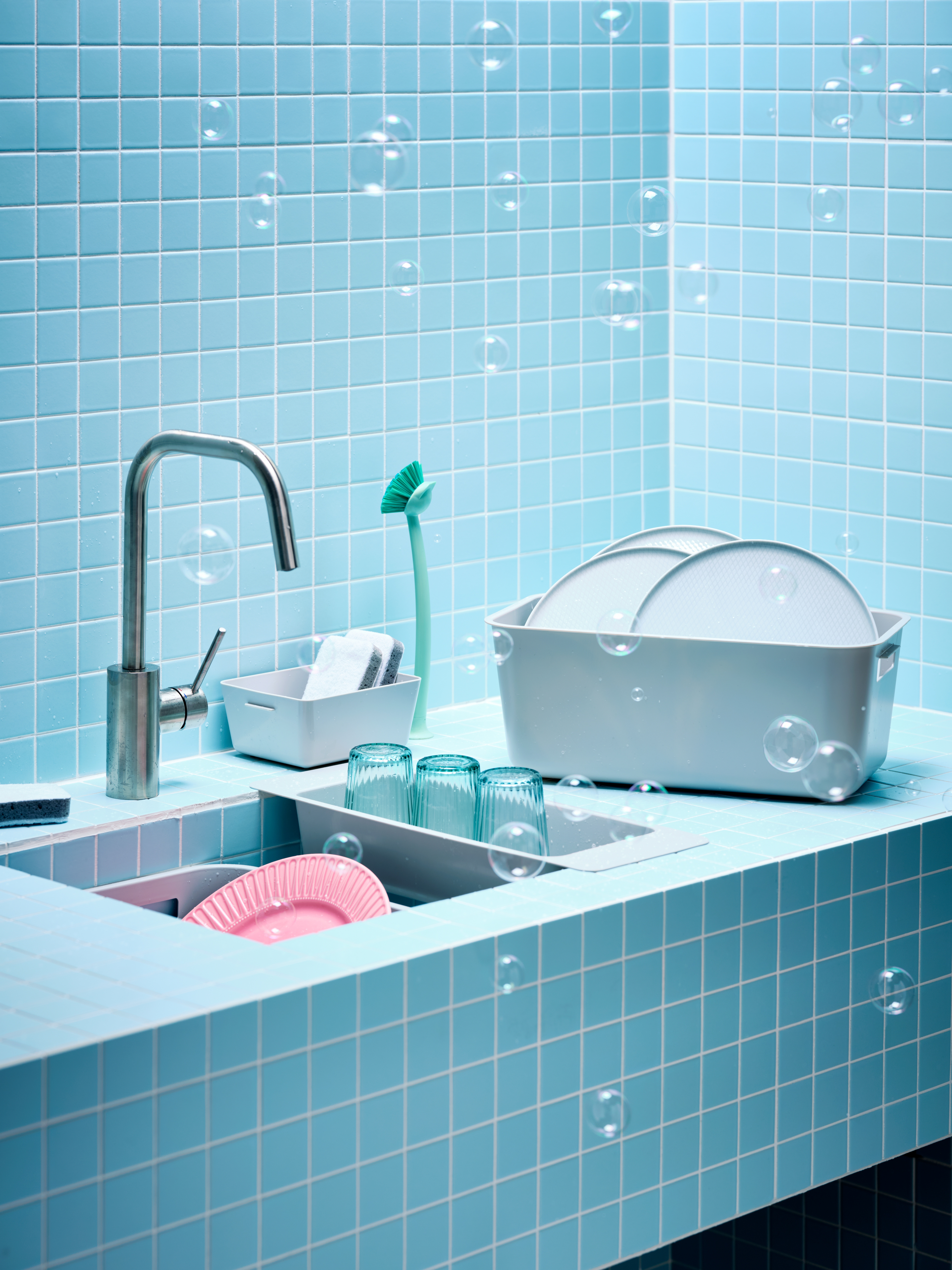 Blue-tiled kitchen worktop with ongoing washing-up with GRUNDVATTNET accessories, pastel tableware and airborne soap bubbles.