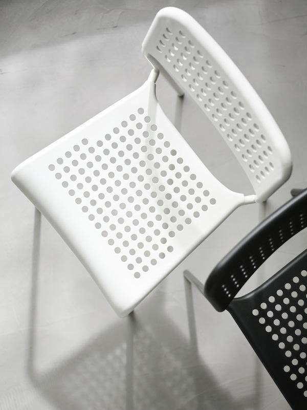 Sedadlá aopierky čiernej abielej stoličky ADDE, ktoré sú postavené vedľa seba, no každá je otočená opačným smerom.