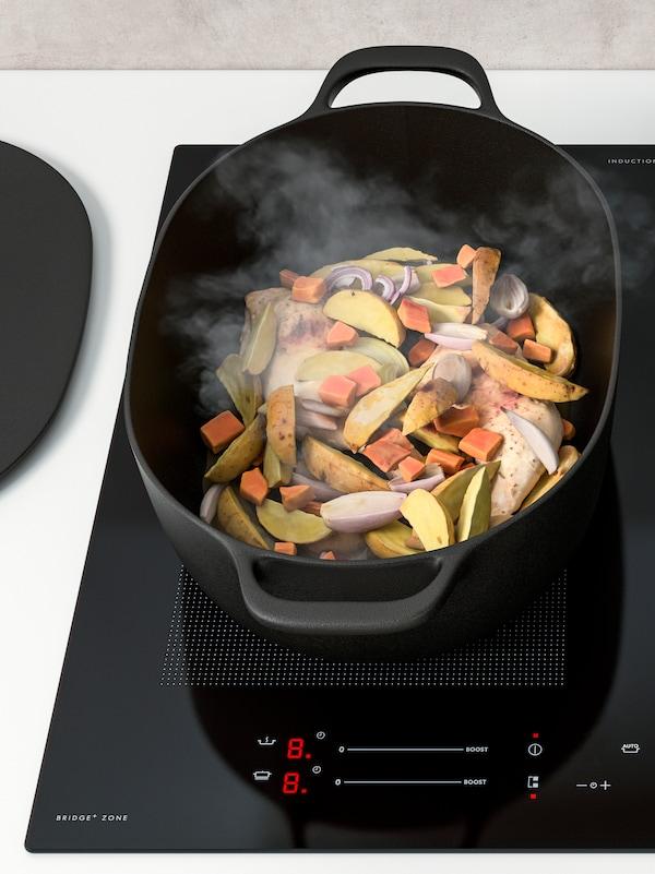 Auf einem Induktionskochfeld wird in einem schwarzen VARDAGEN Bratentopf ein Eintopf aus Gemüse, Kartoffeln und Hühnchen gekocht.