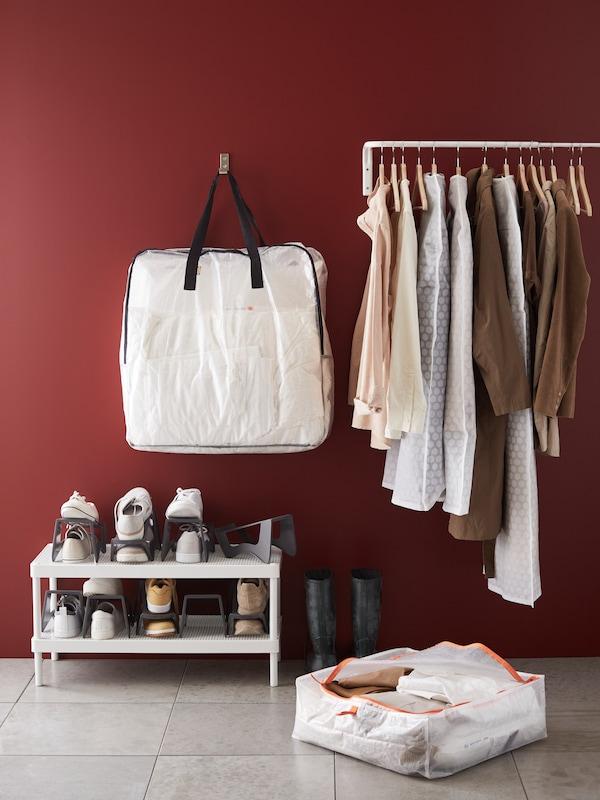 enmörkröd vägg med maassor av klädförvaring framför, både vägghängd med en massa kläder på samt skor på en skohylla, på golvet ligger en låda med förvaring inuti
