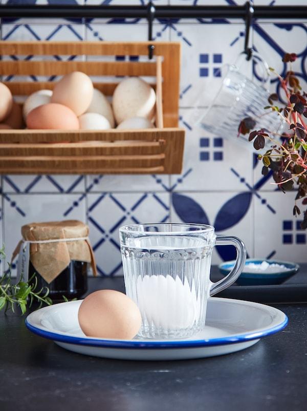 Dous ovos nun prato sobre o que descansa unha cunca de vidro DRÖMBILD chea de auga cun ovo no fondo.