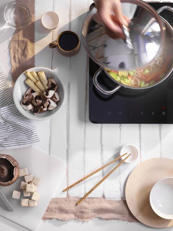 Ruka zvedající víko z hrnce se zeleninou na černé přenosné varné desce umístěné na bílém stole s hrnky a hůlkami.