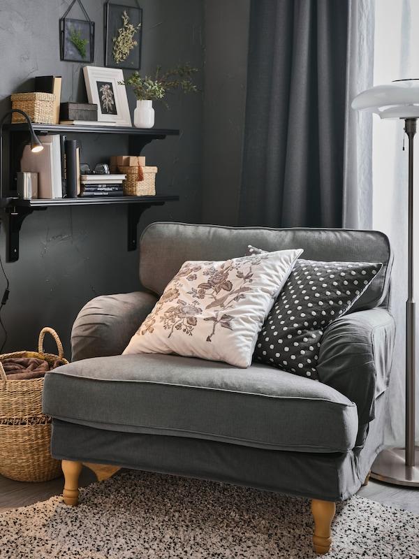 STOCKSUND lænestol med 2 ekstra puder står i et hjørne i nærheden af 2 sortbrune BERGSHULT hylder på en væg.