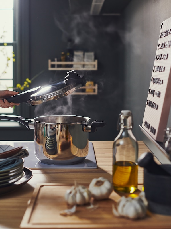 An IKEA 365+ Pot sits on an induction hob, in a bring  kitchen. Preparing food for the festival
