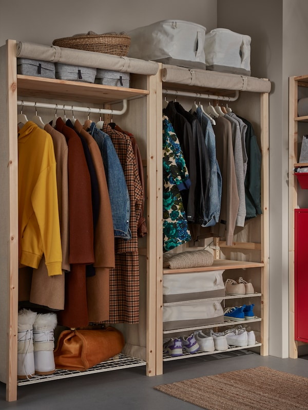 An IVAR storage unit with shelves, rail and rolled-up cover. Clothes hang on the rails, with shoes and boxes on the shelves.
