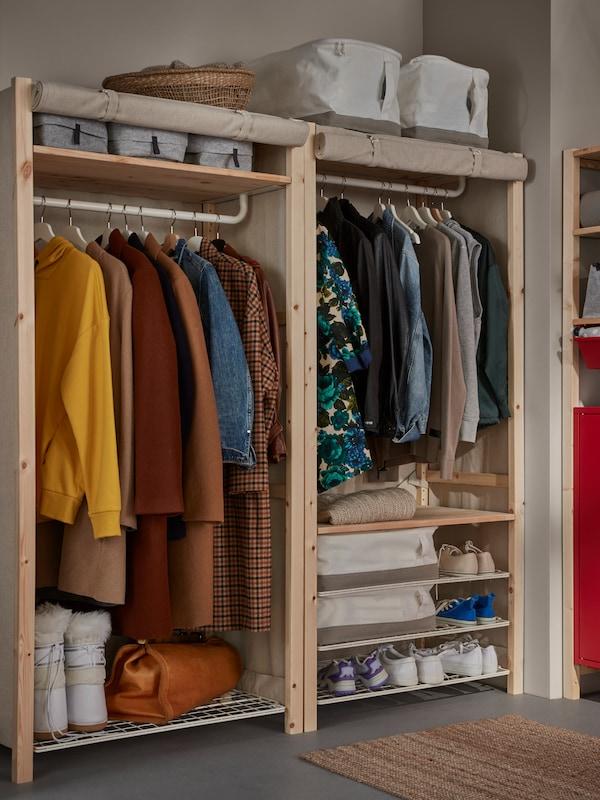 Un rangement IVAR avec tablettes, tringle et housse enroulée. Des vêtements sont suspendus sur les tringles, des chaussures et des boîtes sont posées sur les étagères.