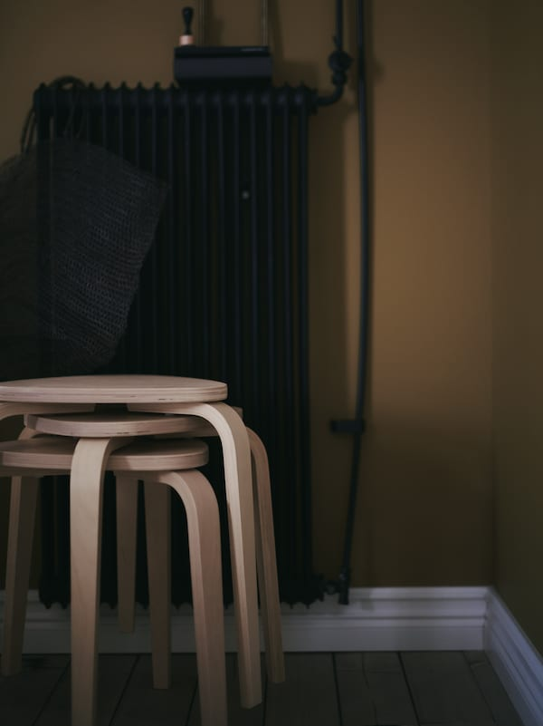 A stack of KYRRE stools in birch, in front of a dark coloured metal radiator with a bag hanging from it.