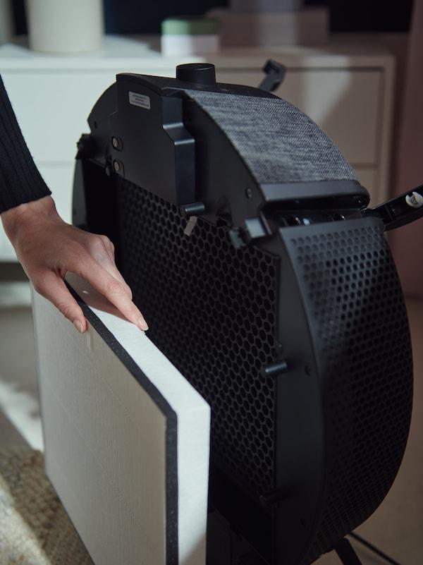Egy nő éppen kiveszi a szűrőt egy fekete, padlóra tehető STARKVIND légtisztító modell elejéből.