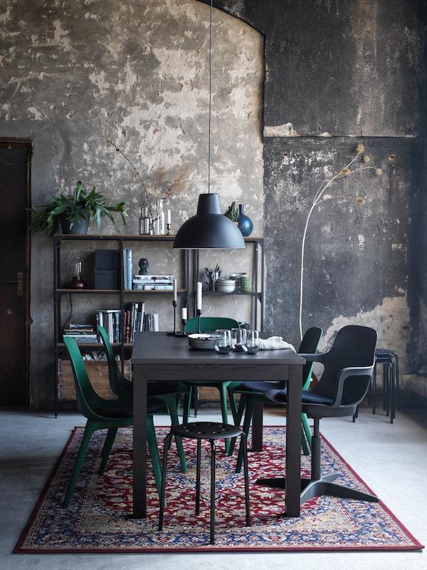 Un coin à manger meublé d'une table LANEBERG brune et de différents tabourets et chaises, le tout installé sur un tapis VEDBÄK multicolore.