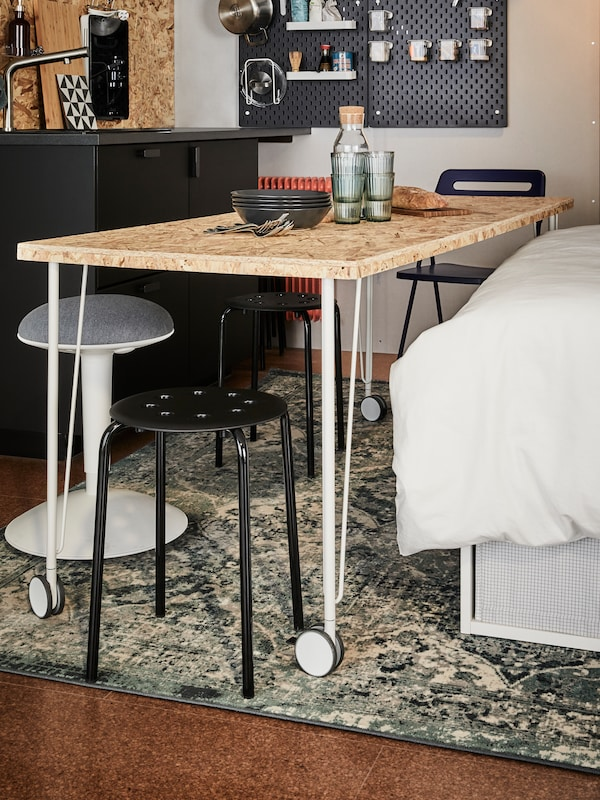 A wooden tabletop on white legs with castors, between a bed, two black stools and a white/grey NILSERIK standing support.