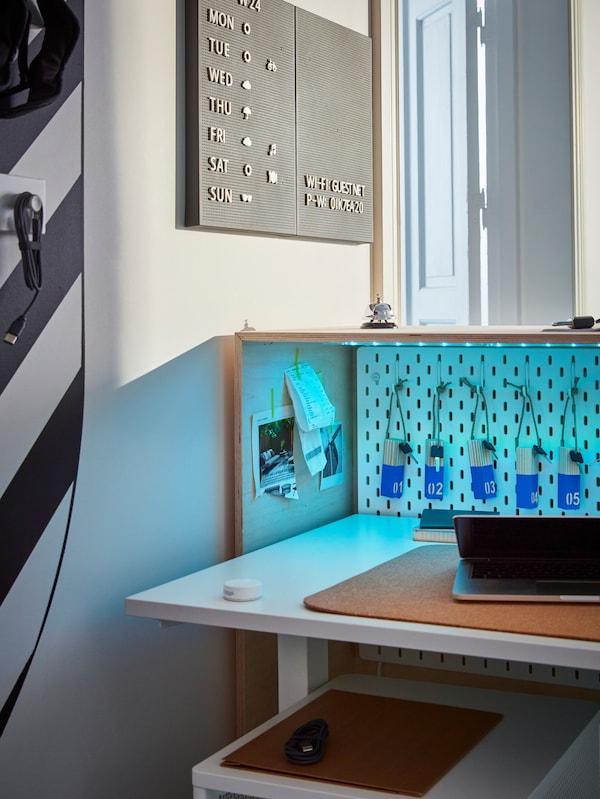 Dietro al banco di accettazione una scrivania regolabile in altezza con laptop e le chiavi delle stanze appese alla parete.