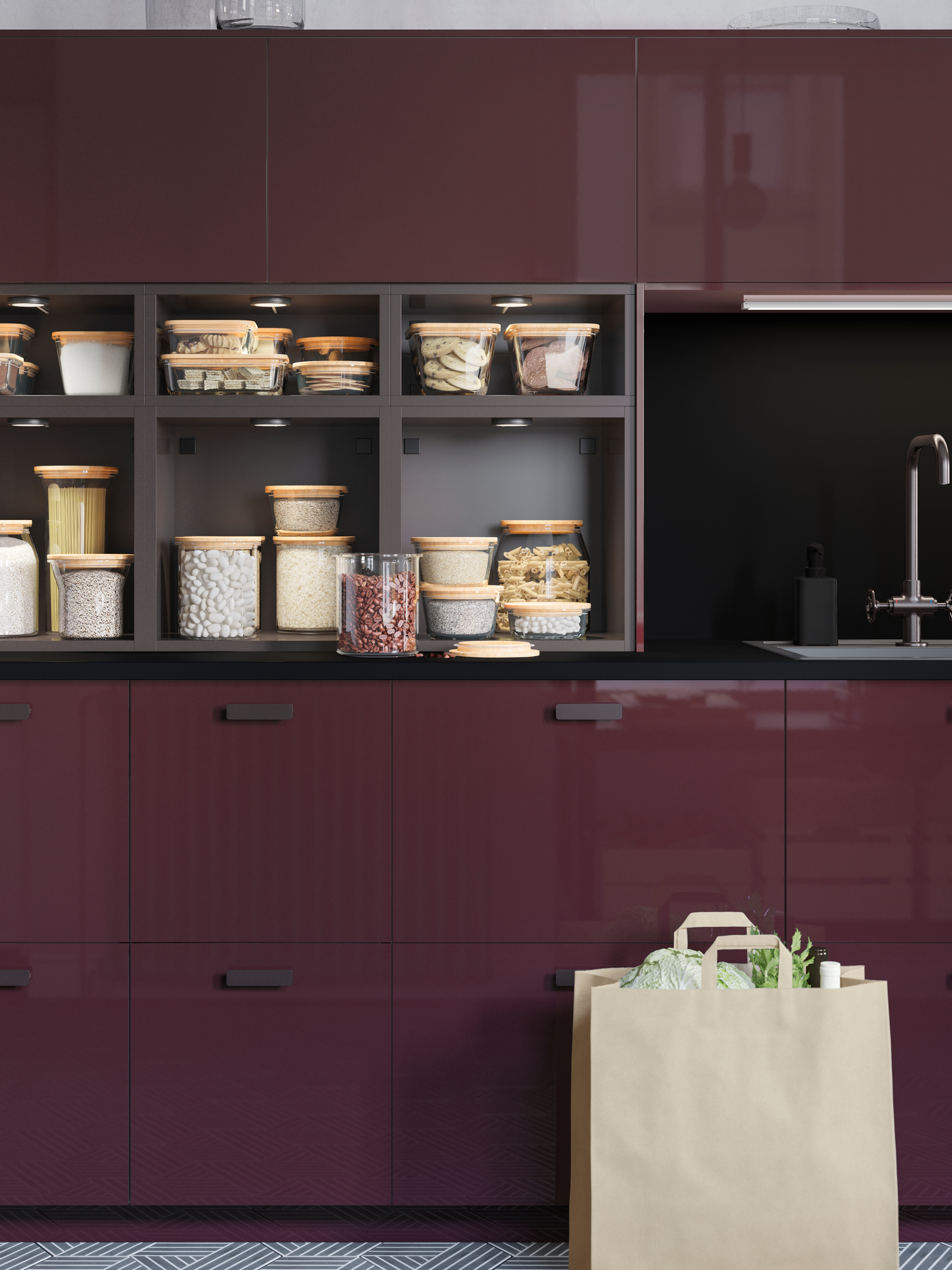 A kitchen with KALLARP high-gloss dark red-brown drawers and open cabinets in anthracite displaying food in glass jars.