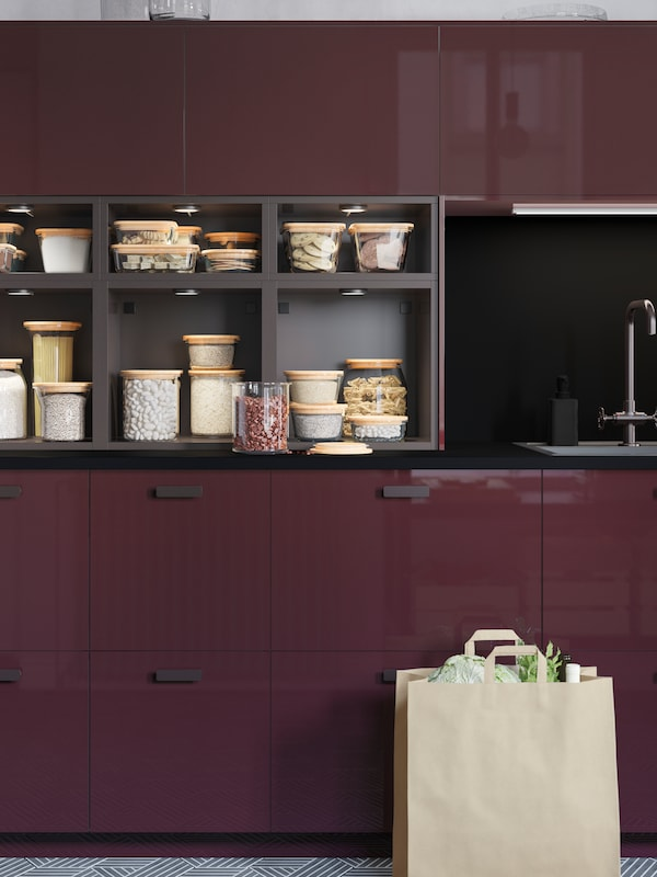 A kitchen with high-gloss drawers and doors in burgundy and open cabinets in anthracite displaying food in glass jars.
