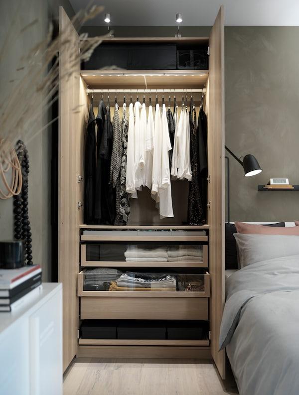 Un dulap PAX din lemn bej, cu ușile deschise, în care sunt vizibile accesorii interioare și sertare personalizate.