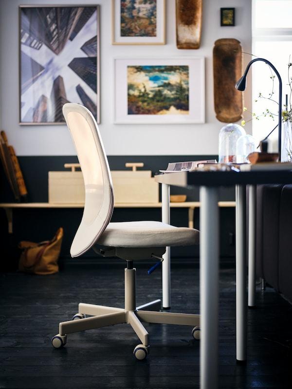 Ein FLINTAN Drehstuhl in Beige steht an einem Schreibtisch mit einer dunkelgrauen LAGKAPTEN Tischplatte in einem Raum mit gerahmter Kunst an den Wänden.
