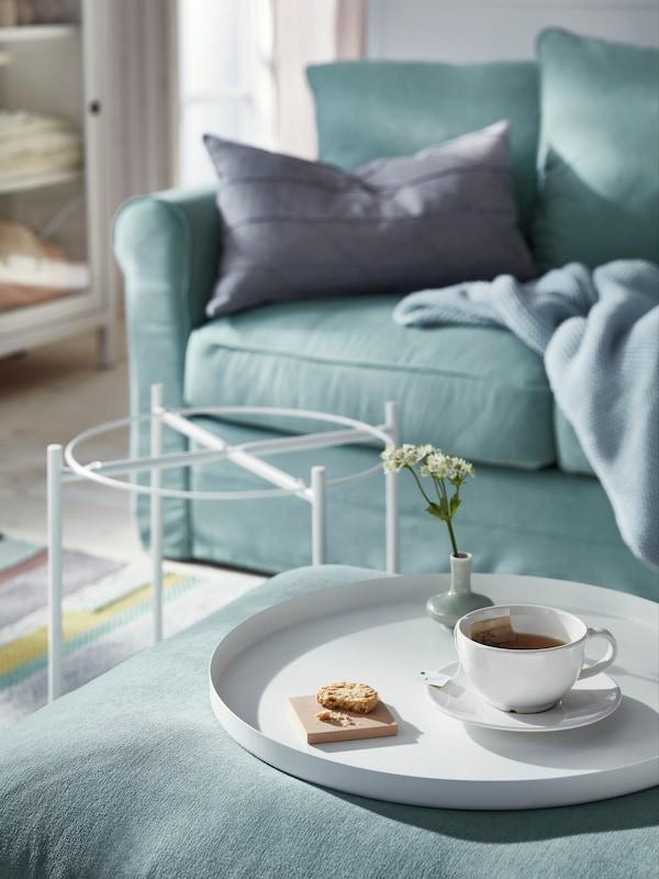 GLADOM Tavolino vassoio bianco, adagiato sopra un pouf turchese, all'interno di un soggiorno - IKEA