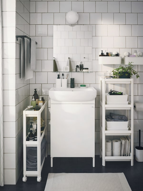 White NYSJÖN bathroom furniture, white VESKEN shelf unit and white TISKEN baskets with suction cup in a small bathroom.
