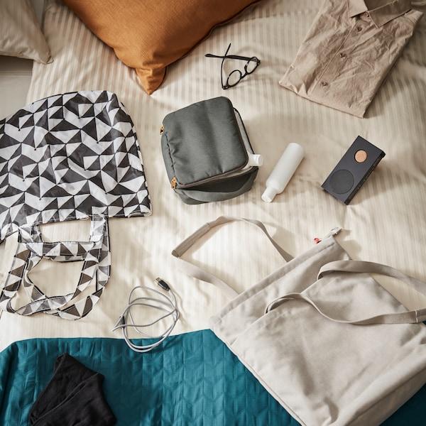 Verschiedene Reiseutensilien und faltbare SKYNKE Einkaufstasche auf einem Bett ausgebreitet.