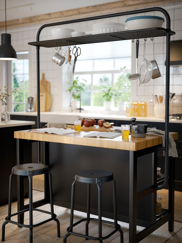 A freestanding kitchen island in black/wood with a thick wooden worktop and kitchen utensils hanging from a rack.