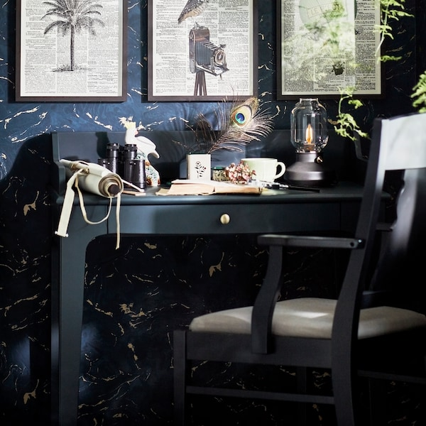 A blue-green LOMMARP desk with a black armchair, with a lamp and diverse items on the table top and frames on the wall.