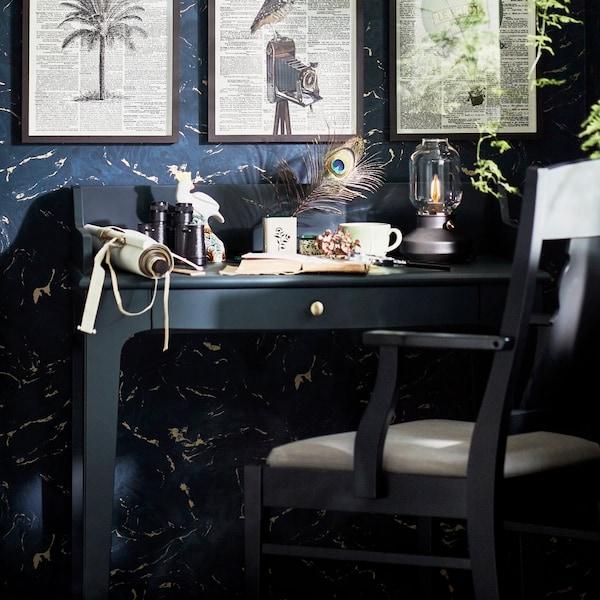Kék-zöld LOMMARP íróasztal fekete karosszékkel, lámpával és különféle tárgyakkal az asztallapon és keretekkel a falon.