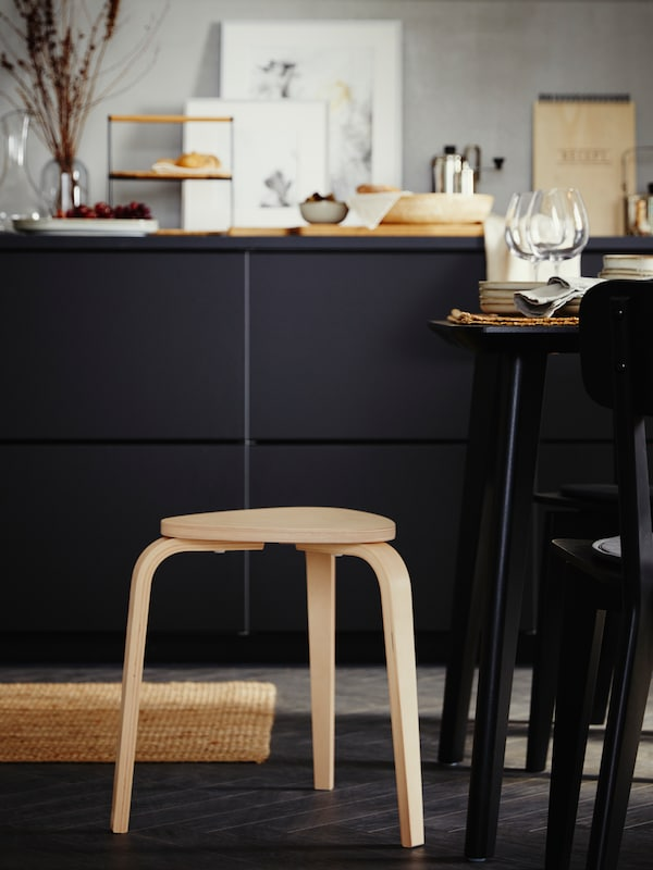 KYRRE low birch stool beside a section of a black table set with glasses and plates, with black kitchen cabinets behind.