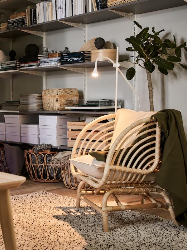 アッシュ材突き板のコーヒーテーブル、籐製のパーソナルチェア、毛足の長いラグ、本などを置いたウォールシェルフがあるリビングルーム。