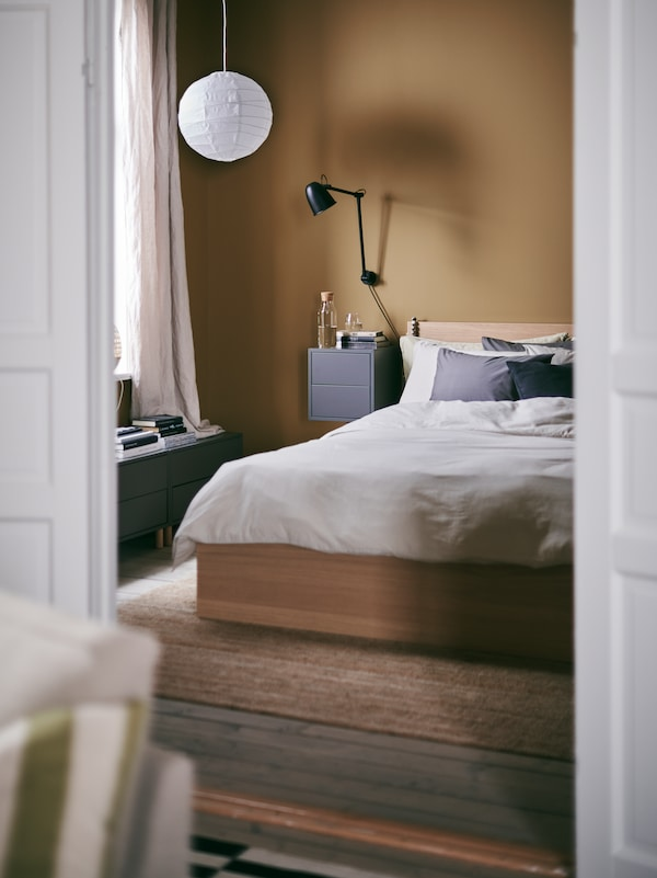 A glimpse into a warm and inviting bedroom with a MALM bed and REGOLIT pendant lamp shade made from paper.