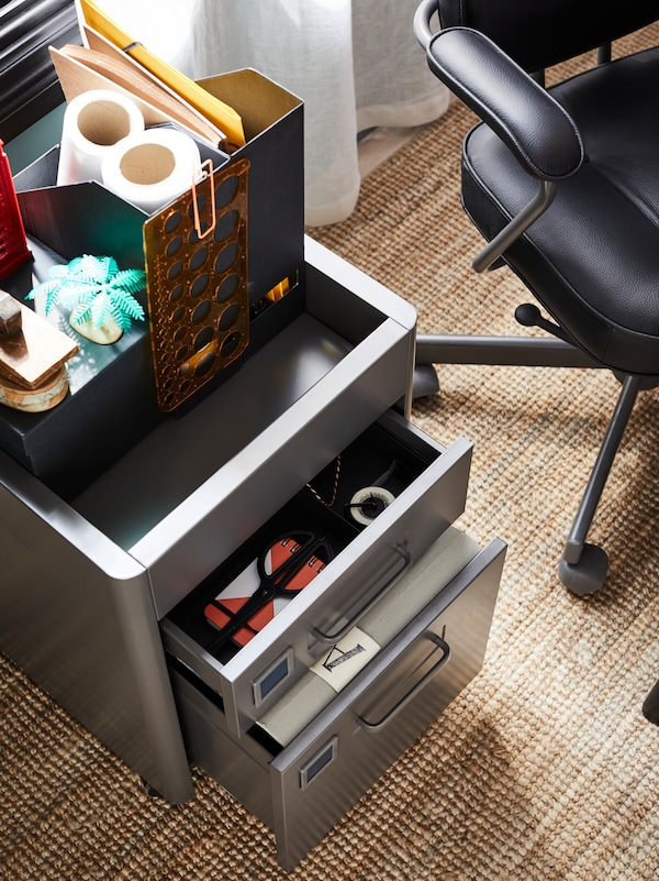 A black chair beside a storage unit, drawers open, holding files and items with various office supplies on the top.