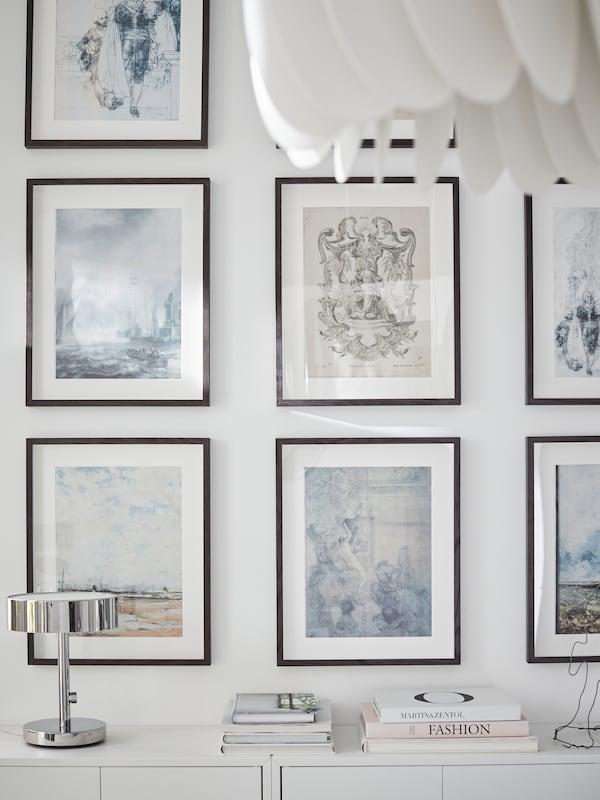 Rame HOVSTA maro închis de la IKEA aranjate la nivel pe peretele alb al camerei de zi.