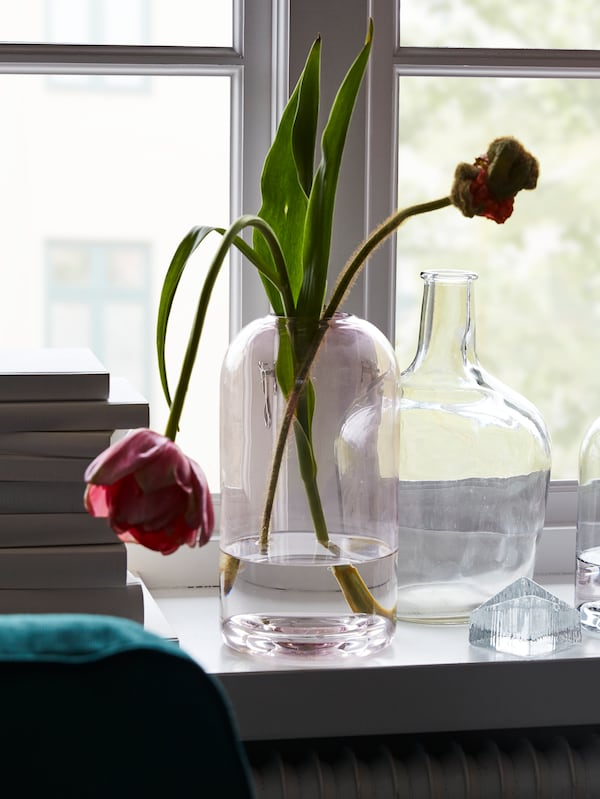 Clear and pink glass vases with flowers stand on a white window sill, the edge of a pile of books beside them.