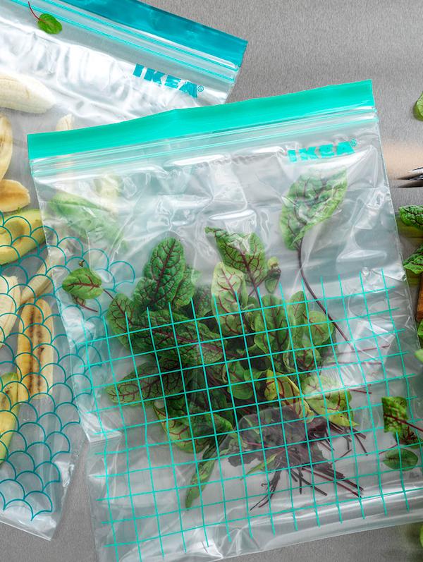 Leżące na blacie torebki strunowe ISTAD w dwóch rozmiarach, z niebieskimi i turkusowymi elementami, wypełnione różnymi ziołami i jedzeniem.