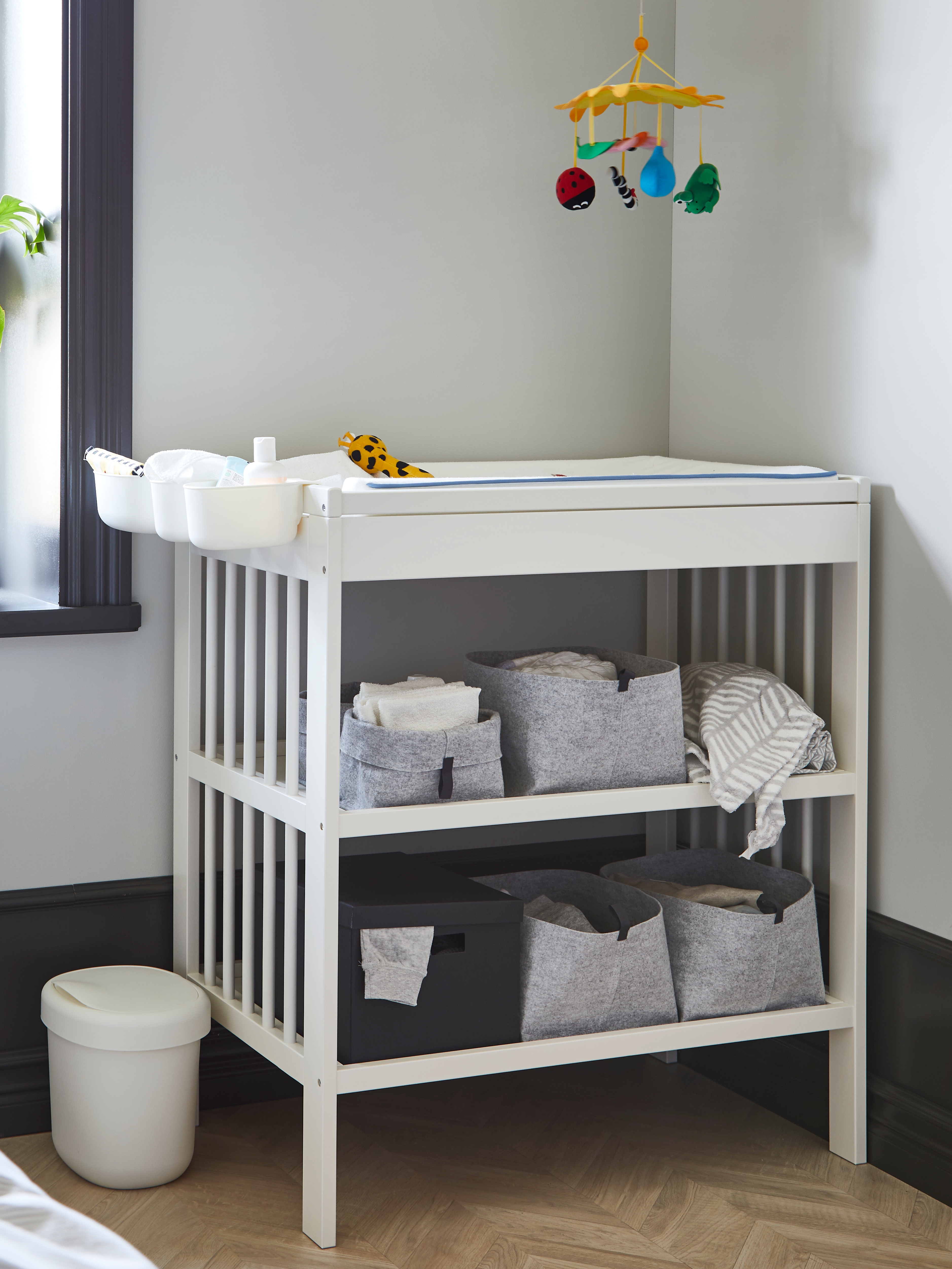 A white GULLIVER changing table with open felt boxes on its shelves and plastic racks of changing supplies hanging on an end.
