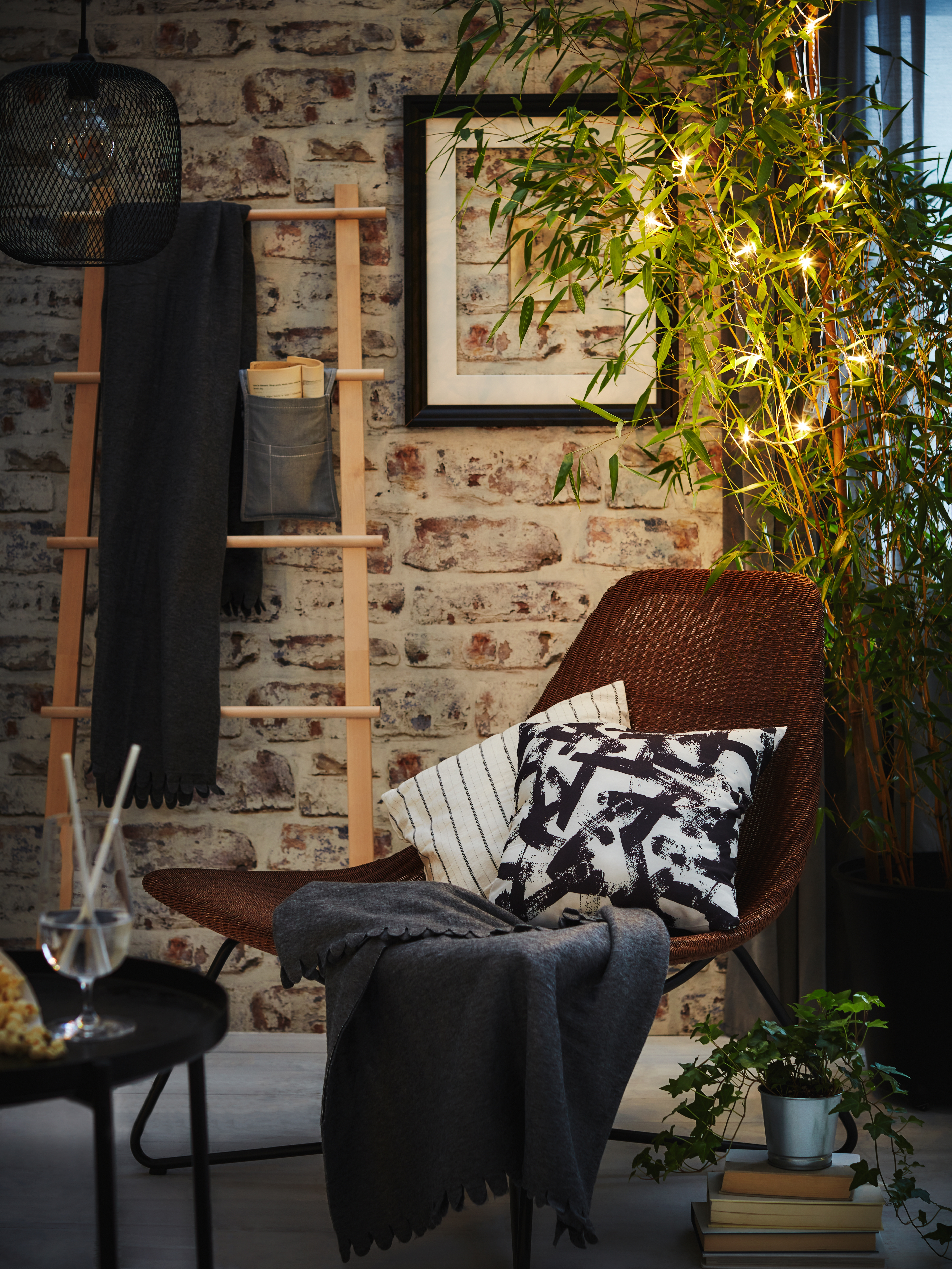 A reading nook surrounded by plants. Books on the floor, a drink on a coffee table and a POLARVIDE throw in the rattan chair.