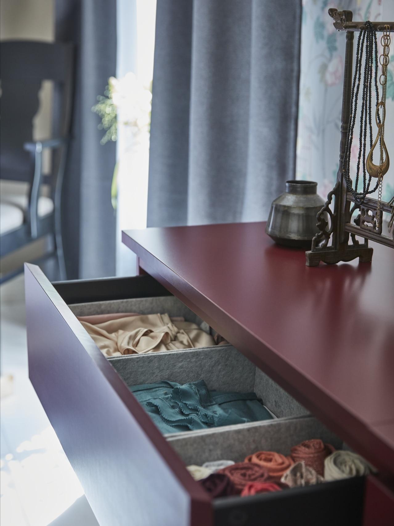 Detalle de una cómoda MALM en rojo oscuro de tres cajones, de los que el primero está abierto para dejar ver tres cajas de fieltro que contienen prendas de seda.