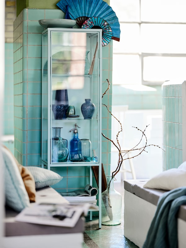 A light turquoise RUDSTA glass-door cabinet by a large window, filled with vases and other objects.