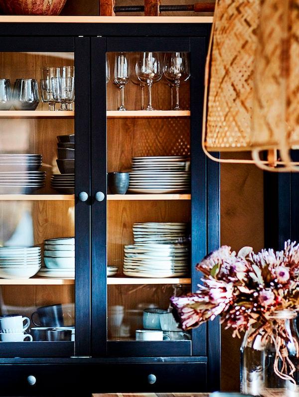 A HEMNES üvegajtós szekrény, benne étkészlettel, néhány vázában lévő virág és egy KNIXHULT függőlámpa lóg a közelében.
