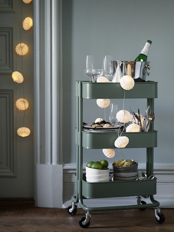 A RÅSKOG cart in gray green with three shelves holding glasses, champagne in a cooler, plates, cutlery and bowls of food.