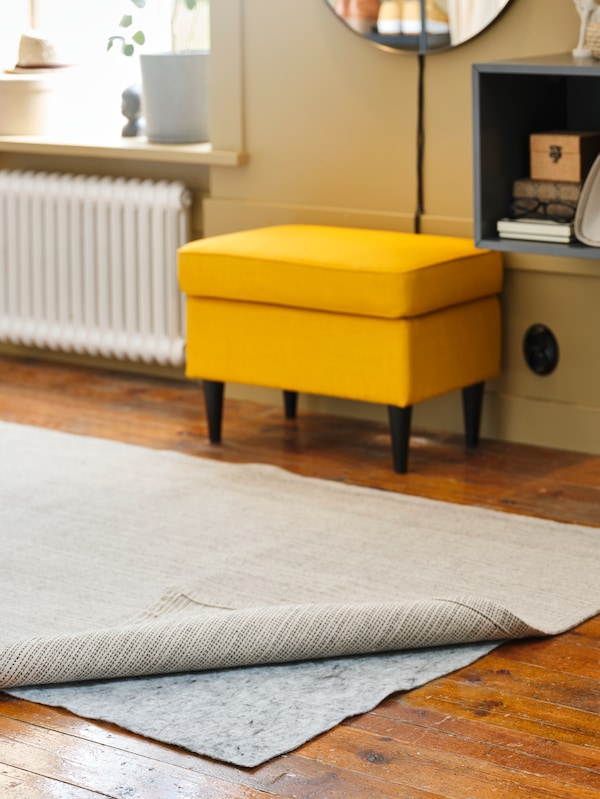 A light brown rug on top of another rug in grey, with the edge of a side table on castors on the grey rug.