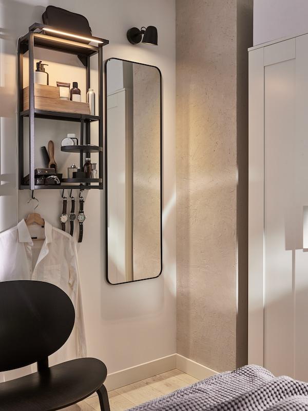 Dinding dengan cermin, lampu dinding dan rangka dinding antrasit dengan para-para dengan kelengkapan tandas, jam dan kemeja digantung padanya.