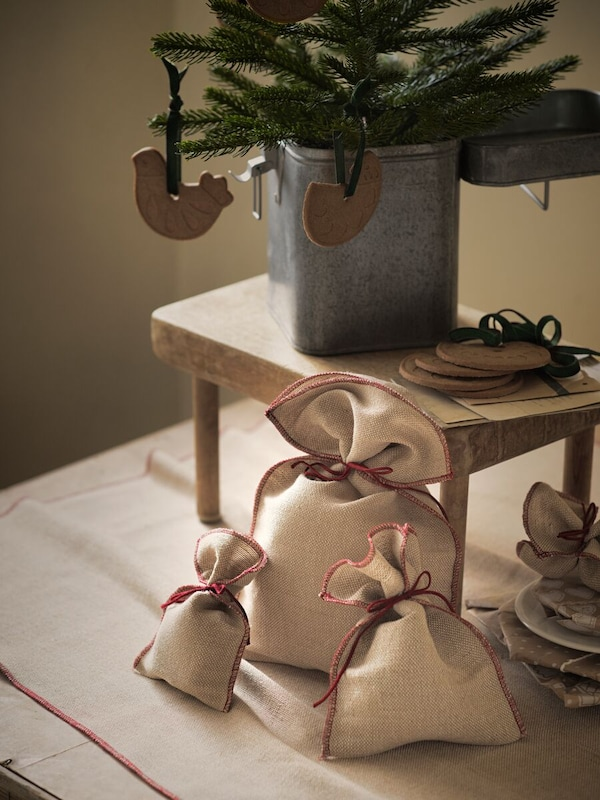 A small wooden table holding a metal box with a seasonal tree in it, decorations hanging from it and gift bags below.
