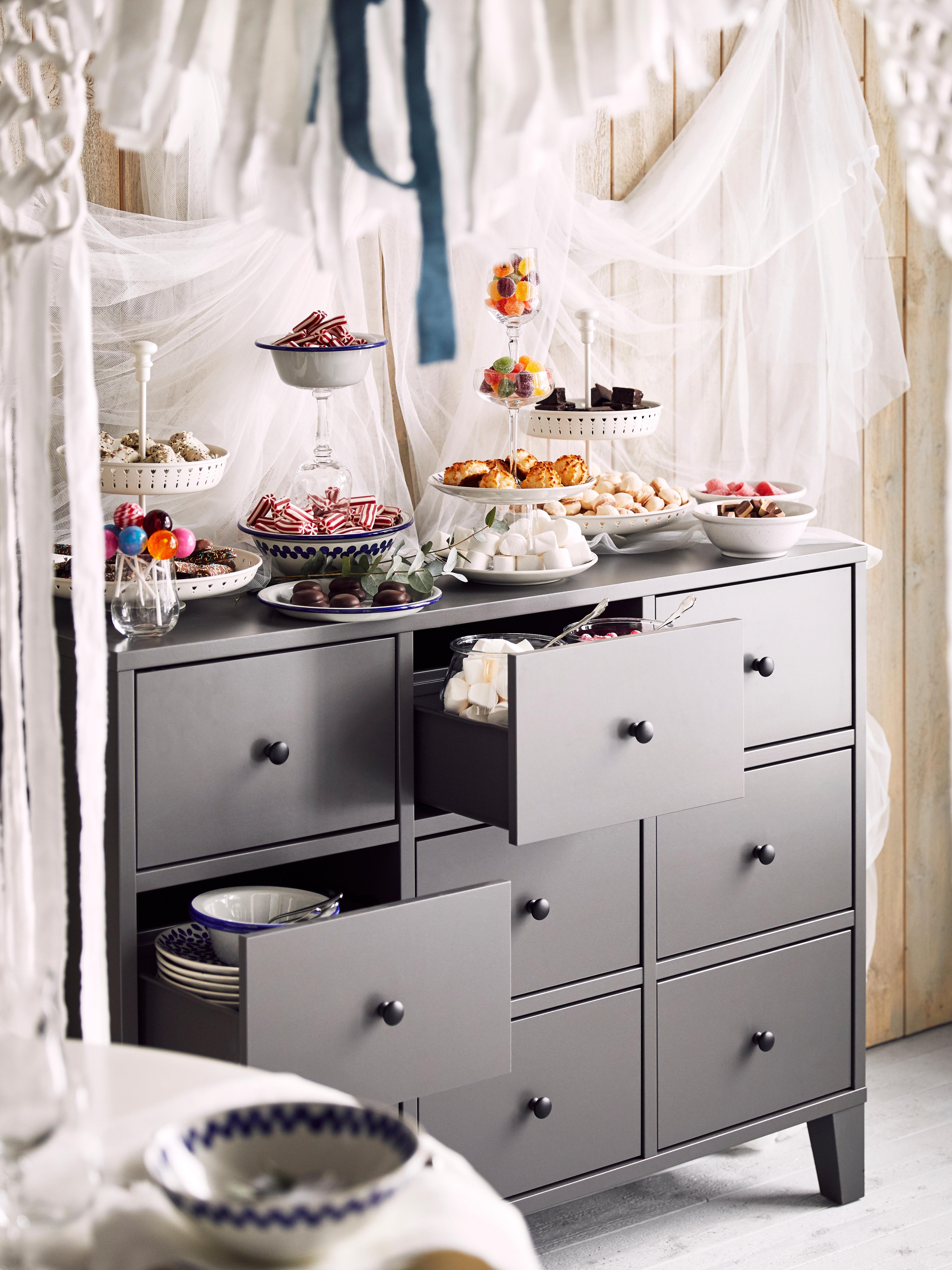 Commode neuf tiroirs BRYGGJA grise avec deux tiroirs ouverts, recouverte de bols et d'assiettes remplis de bonbons.
