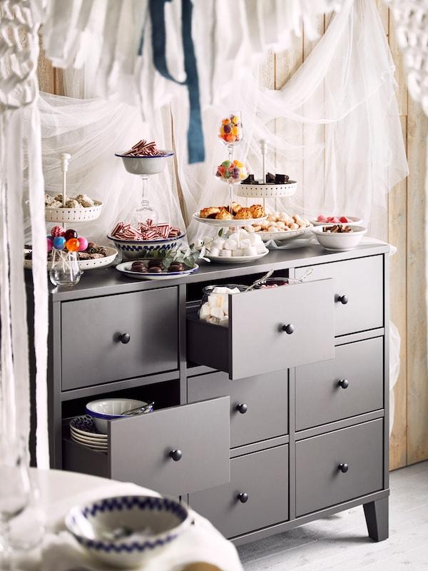Una cómoda BRYGGJA gris con tarros de vidrio, platos y cuencos llenos de dulces en la parte superior y el interior de un cajón.