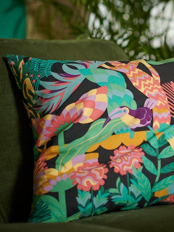 O husă de pernă NÄBBFLY colorată cu un imprimeu cu o pasăre tropicală printre plante exotice și verdeață luxuriantă, așezată pe o canapea din catifea verde.