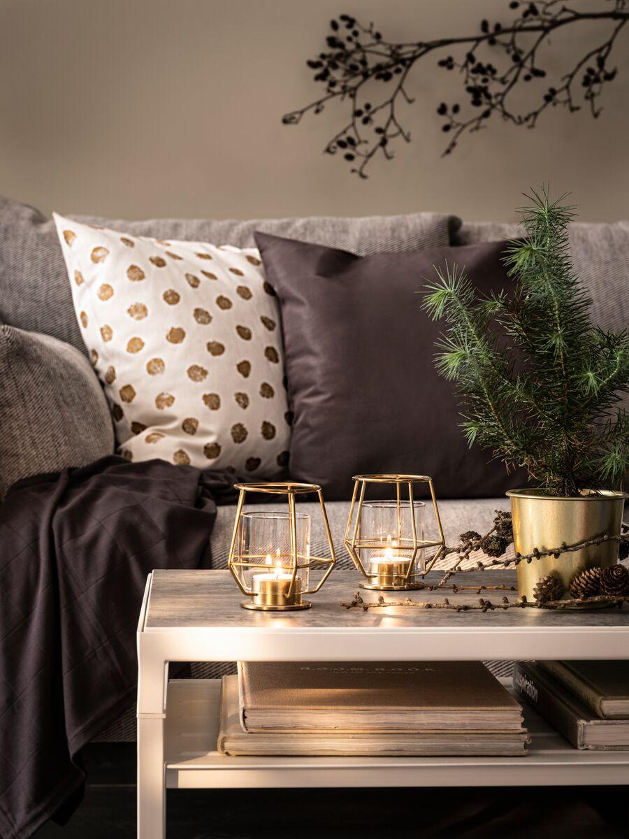 ULLKAKTUS ukrasna jastučnica s točkama, tamnosmeđi jastuk na sivoj sofi sa zimzelenom biljkom i svijećama na stoliću.